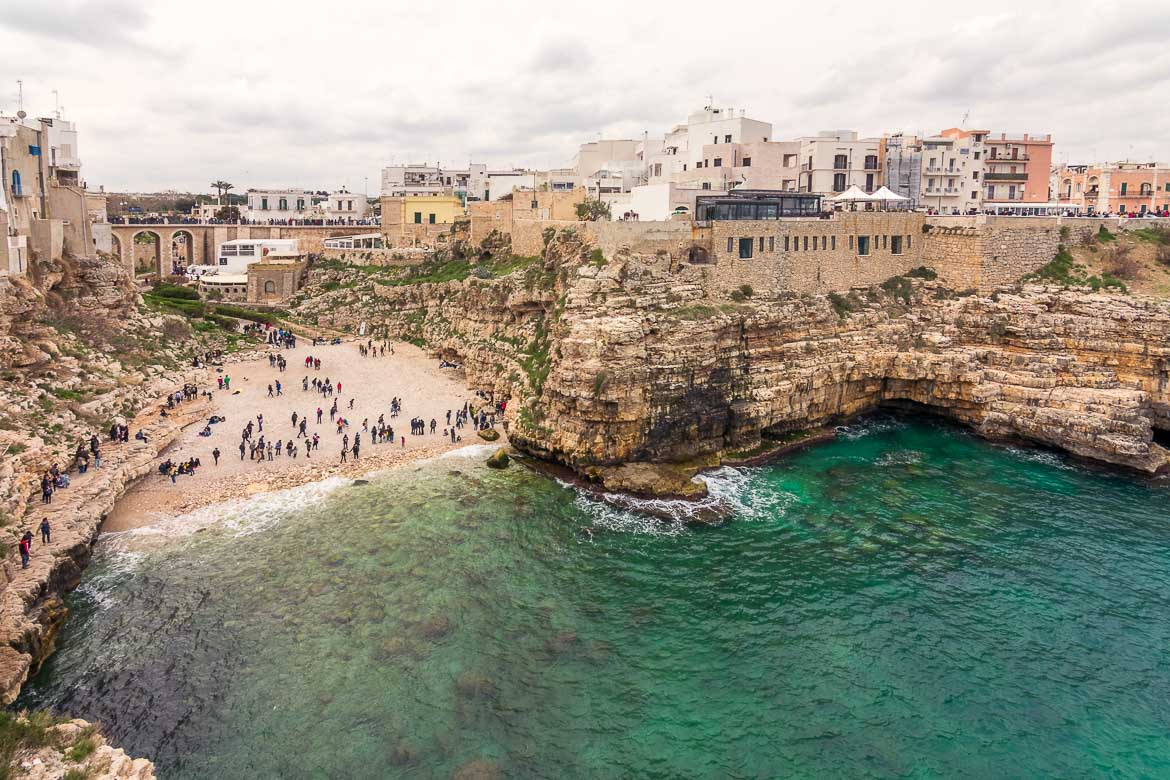 This is a panoramic shot of Polignano a Mare on a cloudy and windy day. There are quite a few people hanging out on the beach as the weather is not suitable for a swim. On both sides of the beach stand tall cliffs with buildings on top.