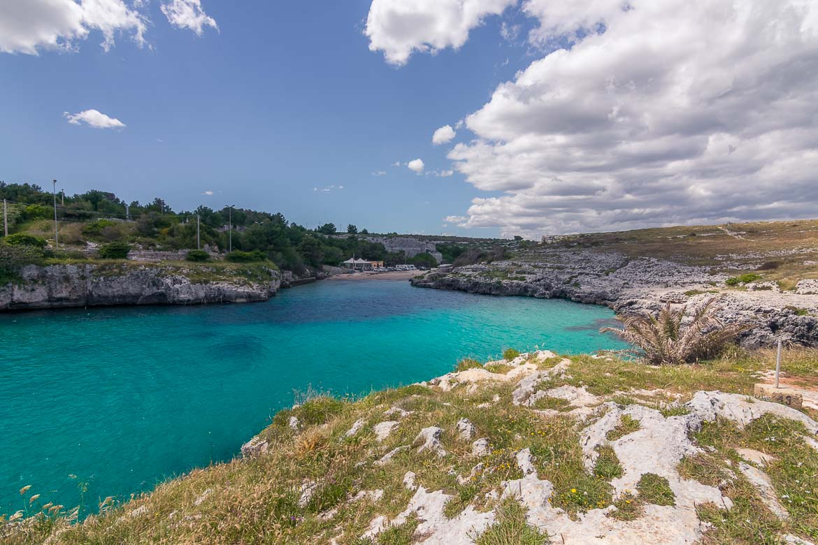 This is a photo of Porto Badisco. It is a small cove with rocks on both sides and emerald waters.