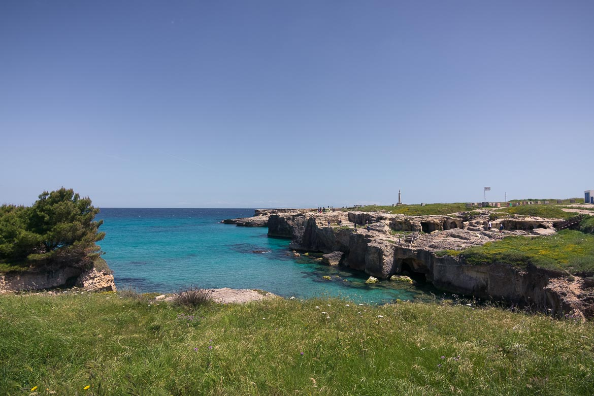 This image shows the wider area of Roca Vecchia. There are rocks with low vegetation above the emerald sea.