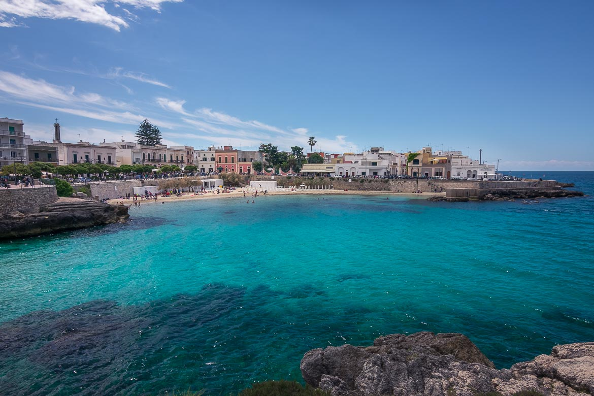 This is a panoramic shot of Santa Maria Al Bagno. The sea has an incredibly emerald water. In the background, colourful mansions soar above the sandy beach.