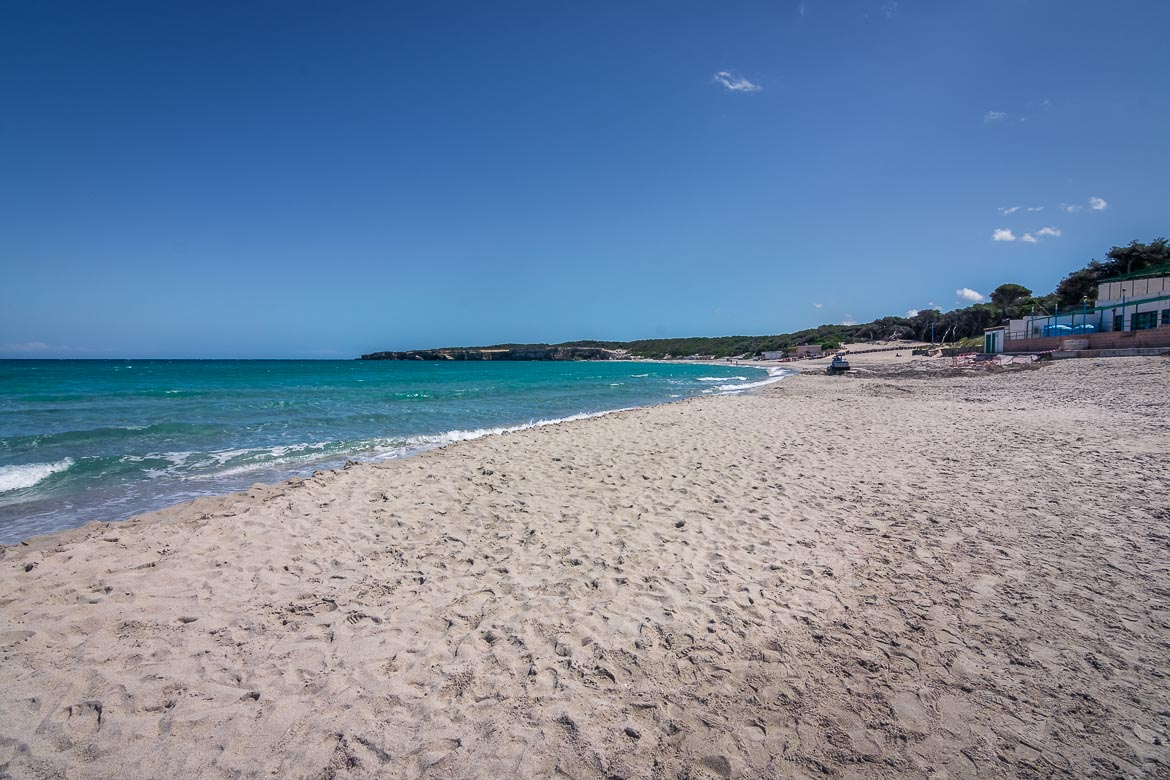 This is a photo of Torre dell'Orso beach. It is a very long beach with white sand. The photo was taken on a sunny yet rather windy day. Therefore, there are waves in the sea and hardly a soul on the beach.
