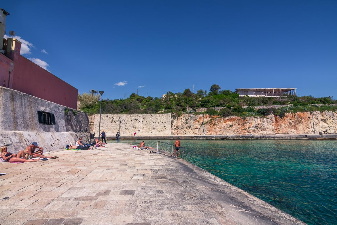 This image shows the quaint little port at Tricase Porto. There are people lying down, taking in the sun and others who swim in the emerald waters.