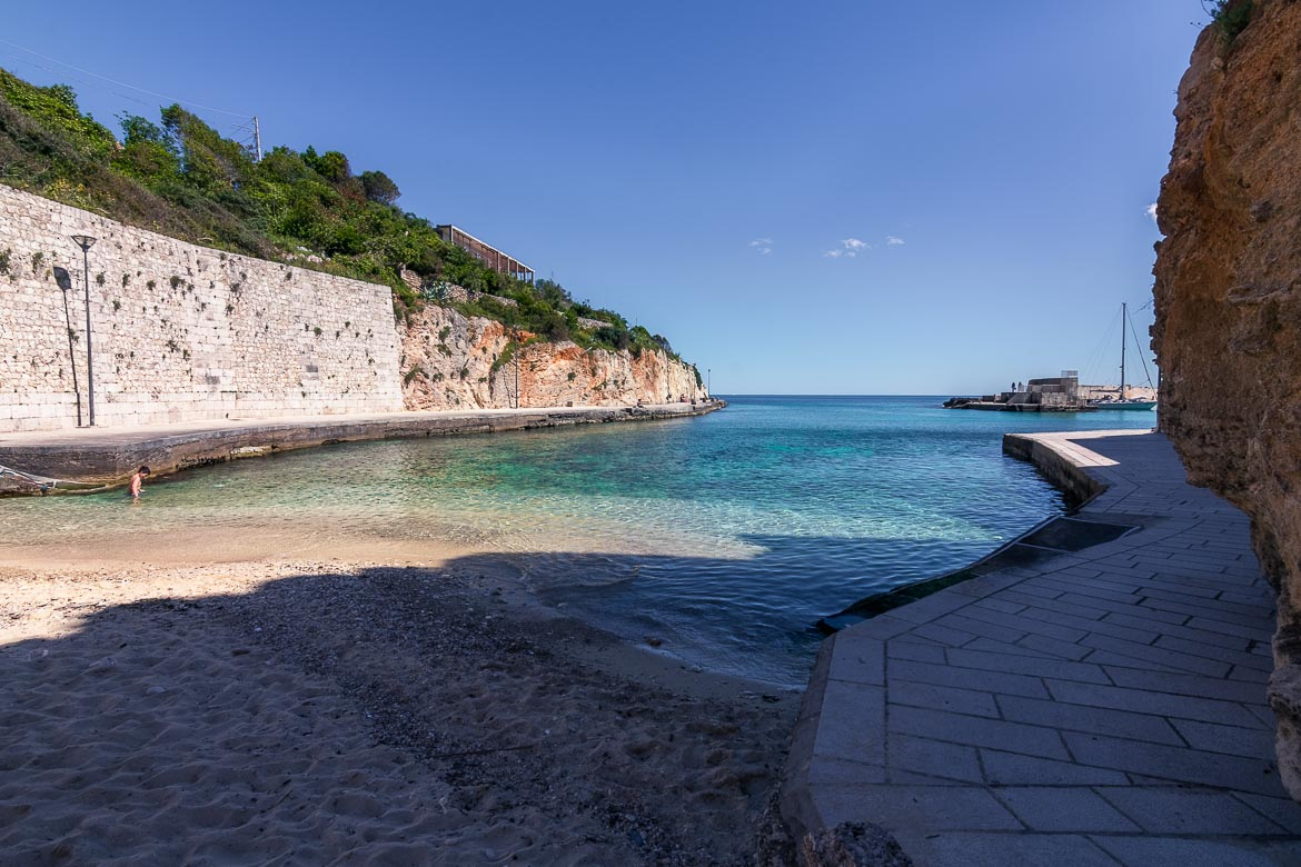 This image shows the small beach at Tricase Porto. The beach is sandy and the waters are emerald. The beach overlooks the port and the wide sea beyond. To our humble opinion, this is one of the best beaches in Puglia Italy.