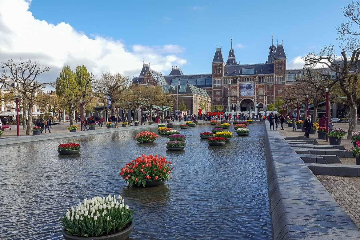 This image shows the Rijksmuseum in Amsterdam. It is a gorgeous ornate red building with an I love Amsterdam sign in front of it as well as a beautiful canal decorated with flowers.