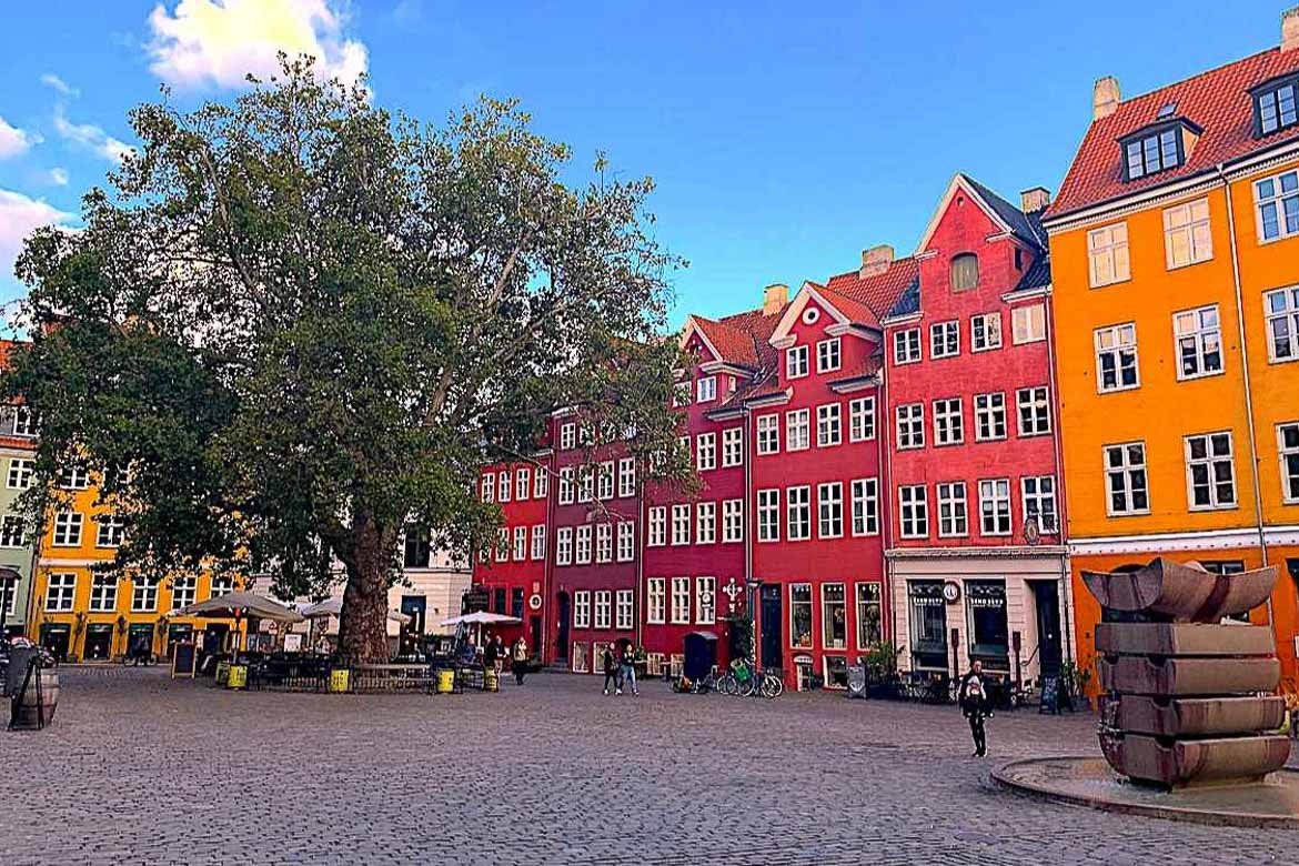 This photo shows a line of brightly coloured buildings on a square in Copenhagen.