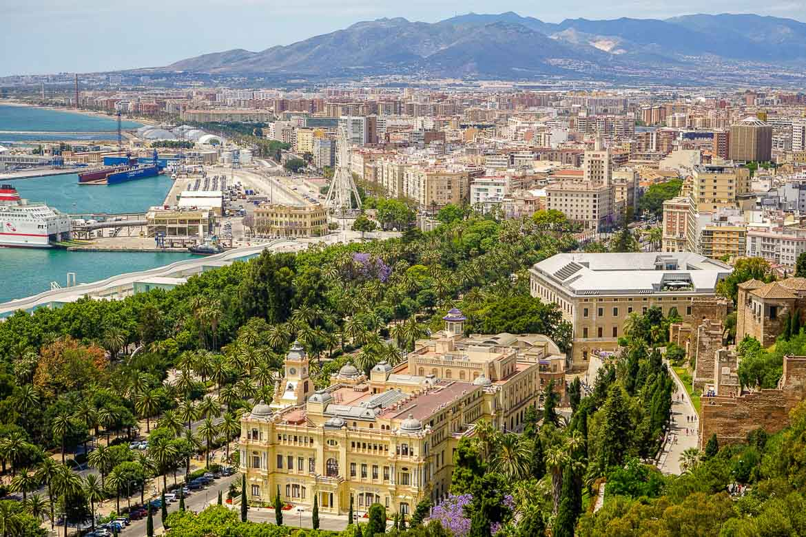 This is a panoramic shot of Malaga. In the foreground, there is a beautiful boulevard lined with palm trees and other trees as well as gorgeous historical buildings. In the background, the modern city as well as part of the port are visible.