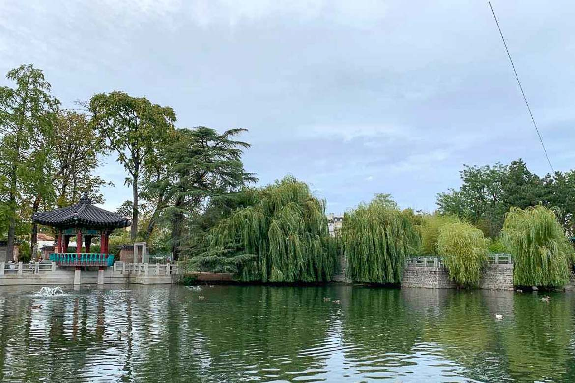 This image shows a small lake on which ducks float in Jardin d' Acclimatation in Paris. The lake is surrounded by trees.