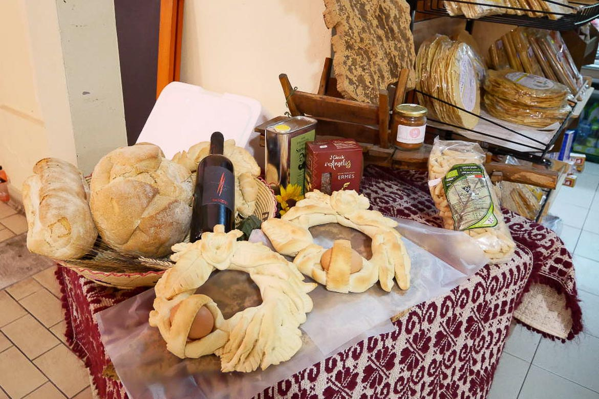This picture shows a table on which there are two round loaves of Sardinia Easter bread. There are also some loaves of plain bread and a bottle of wine.