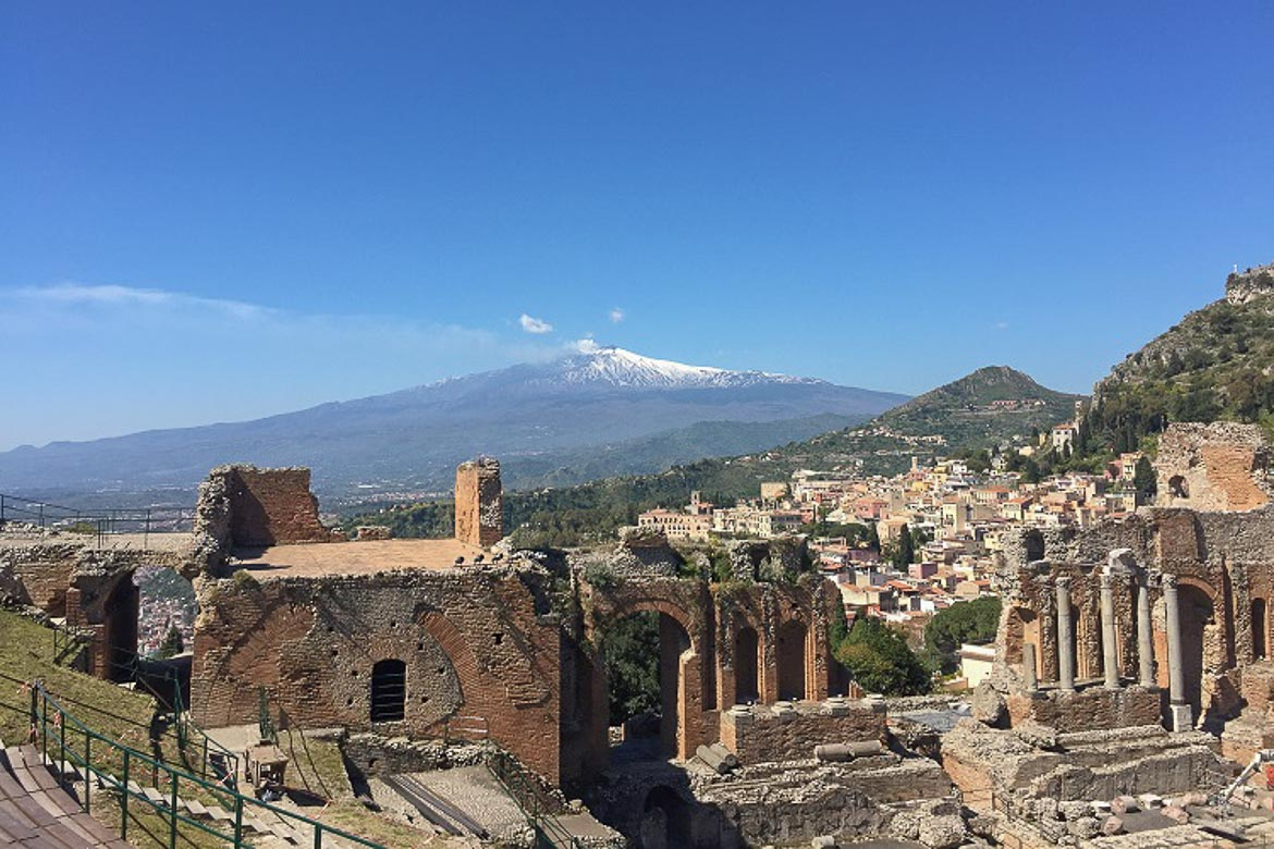 This is an image of the Ruins of the Ancient Greek Theatre in Taormina. In the background, the snowy peak of Mount Etna is visible.