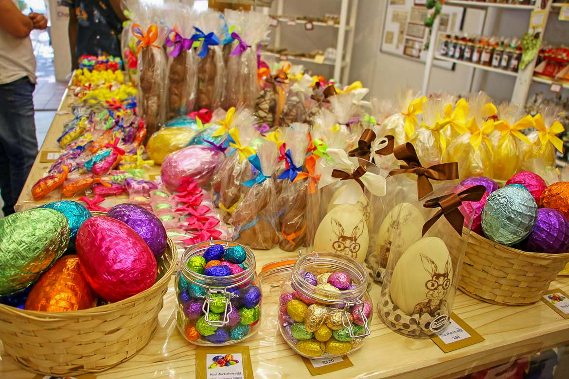 This is a close up of a table full of Easter treats for sale. There are chocolate eggs of all sizes covered in colourful paper. There are also chocolate bunnies and other animals.