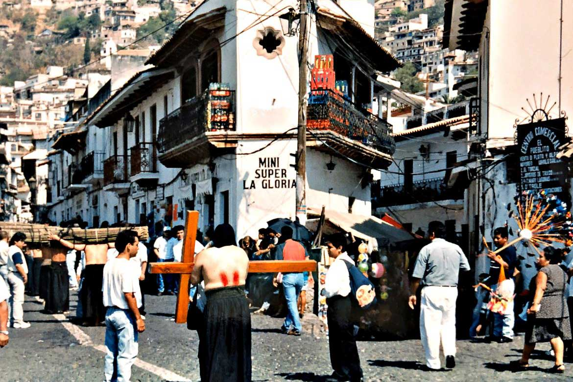 This image shows part of the procession of penitents in Taxco, Mexico. There is one man with his bloodshed back turned to the camera who is carrying a huge wooden cross. There are many spectators at the side of the street.