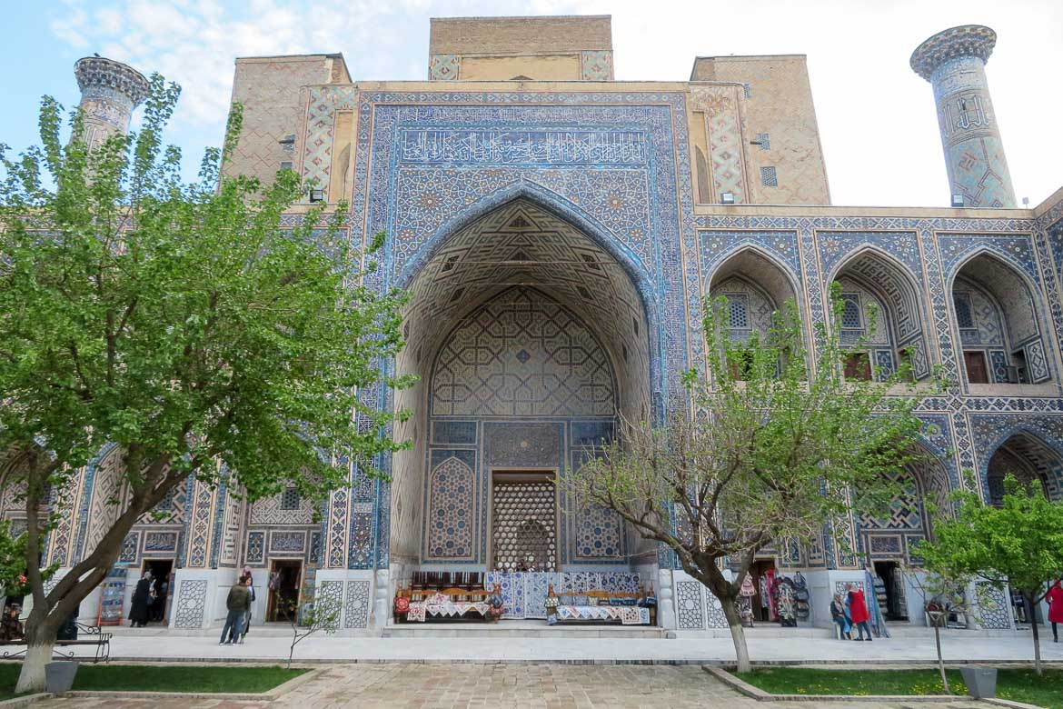 This photo shows a historical building in Samarkand, Uzbekistan. The country boasts unique, breathtakingly beautiful architecture. The madrassa pictured here has a facade covered in light blue and golden tiles.