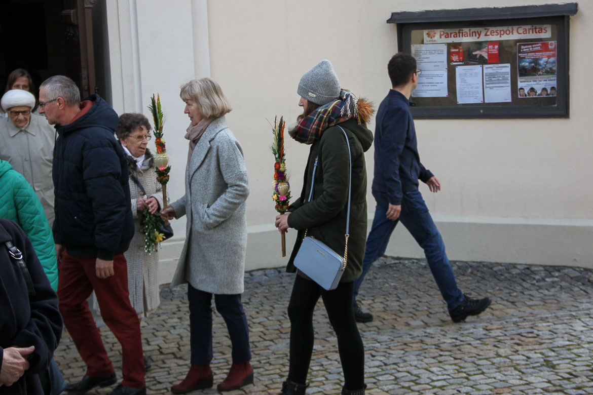 This image shows people outside a church on Palm Sunday holding Polish Easter Palms. The latter are bouquet-like colourful creations.