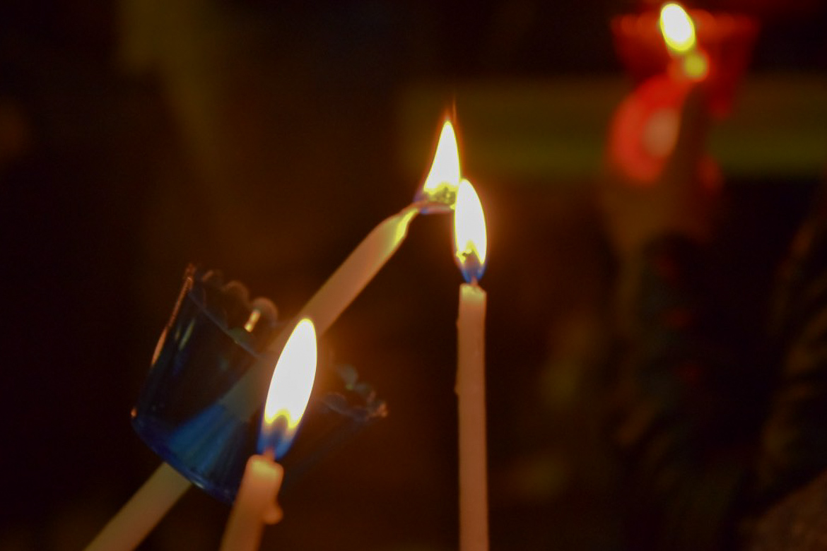 This is a close up of lit candles during a church service in Crete. This is the featured image of our article: The World's 21 best Easter holiday destinations.