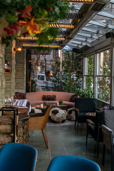 This image was shot inside the cafe at The Peak Hotel in Istanbul. It is early in the afternoon so the cafe is peaceful. The cafe is decorated in blue and earth tones and there are also many plants.