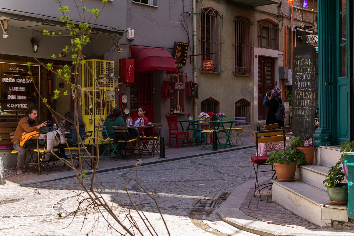 This image shows two quaint cafes with colourful tables and chairs on a cobblestone street. This is Fener neighbourhood in Istanbul, one of the most laid-back and authentic areas in the city.