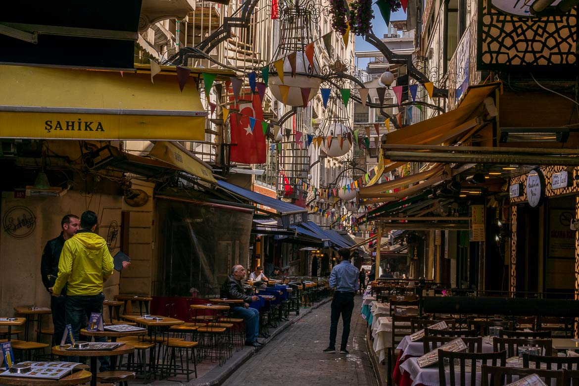 This photo shows a series of pubs and restaurants at Nevizade Street in Istanbul. All the tables and chairs are empty as this area comes alive in the evening. The cobbled street looks very festive with colourful flags and banners hanging above it.