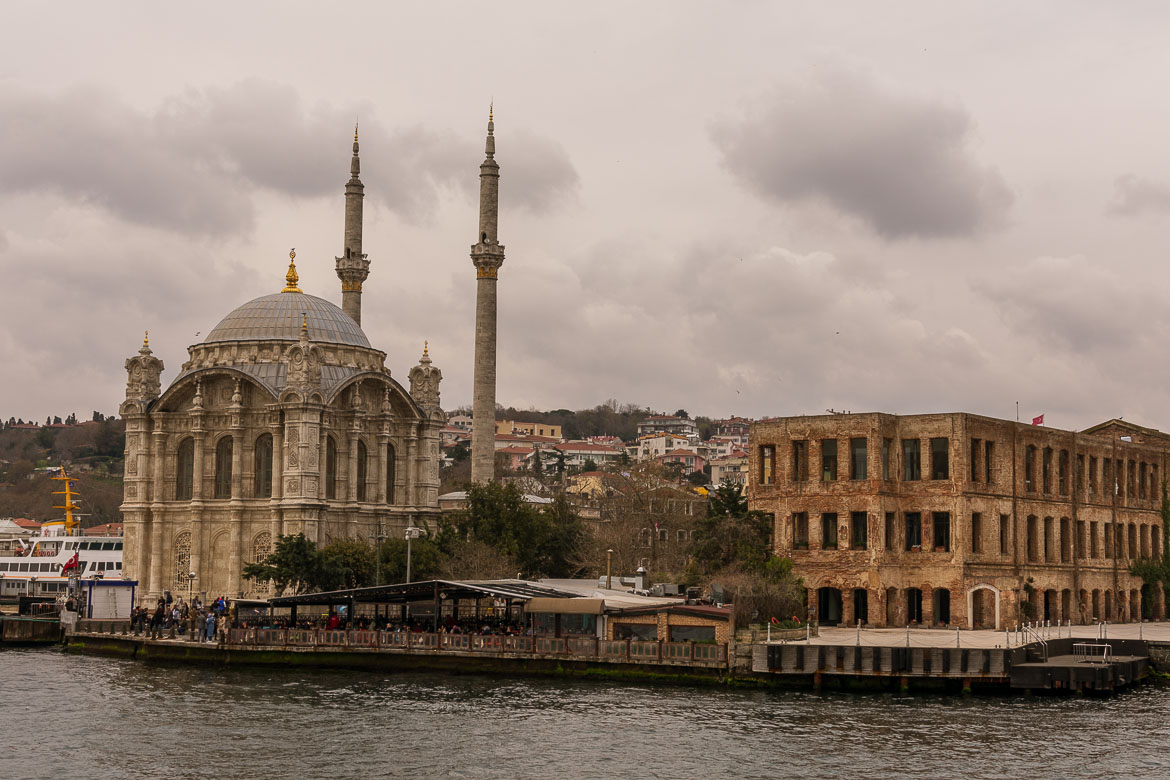 This image shows Ortakoy Mosque in Istanbul. The mosque is an ornate white building with two slender minarets. It is situated on a pier right next to the sea.