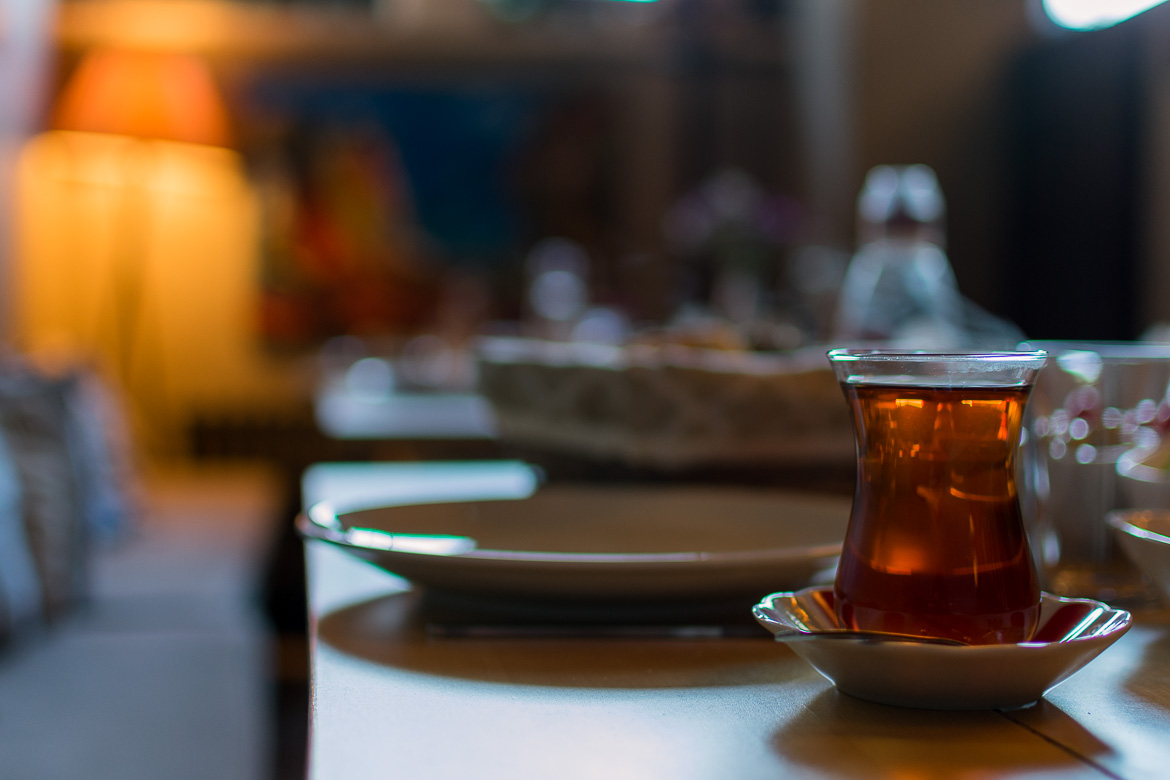 This is an image of the breakfast area at Peradays Hotel. Specifically, the image shows a table with a glass of tea in the foreground.