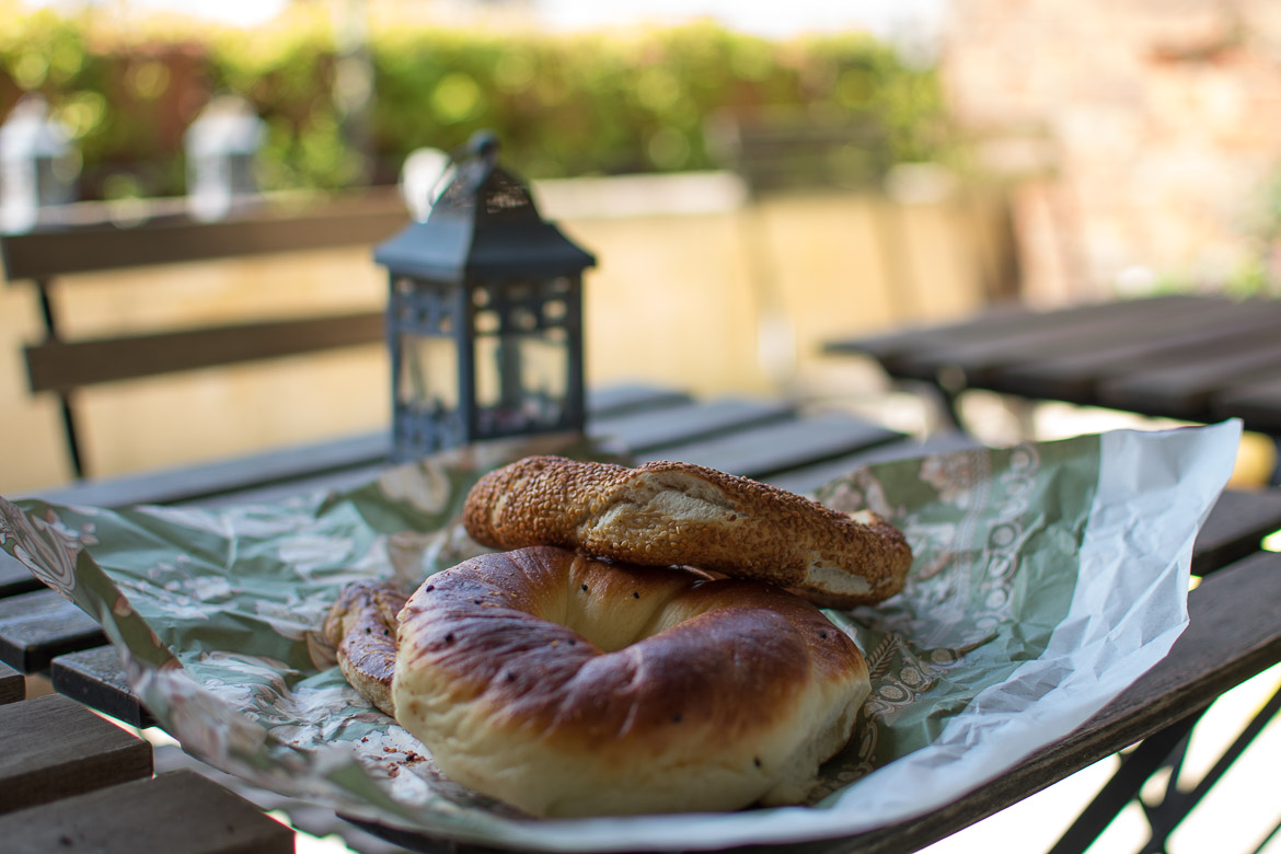 This image shows a simit and an acma, the bagel like snacks of Istanbul. They are on one of the tables at the terrace of Peradays Hotel.