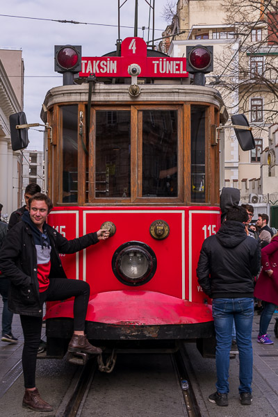 This image shows the red nostalgic tram of Istiklal Avenue in Istanbul with a young man posing in front of it.