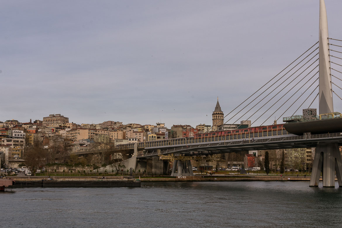 This is an image of the the Halic Metro Bridge on the Golden Horn in Istanbul with Galata Tower in the background.