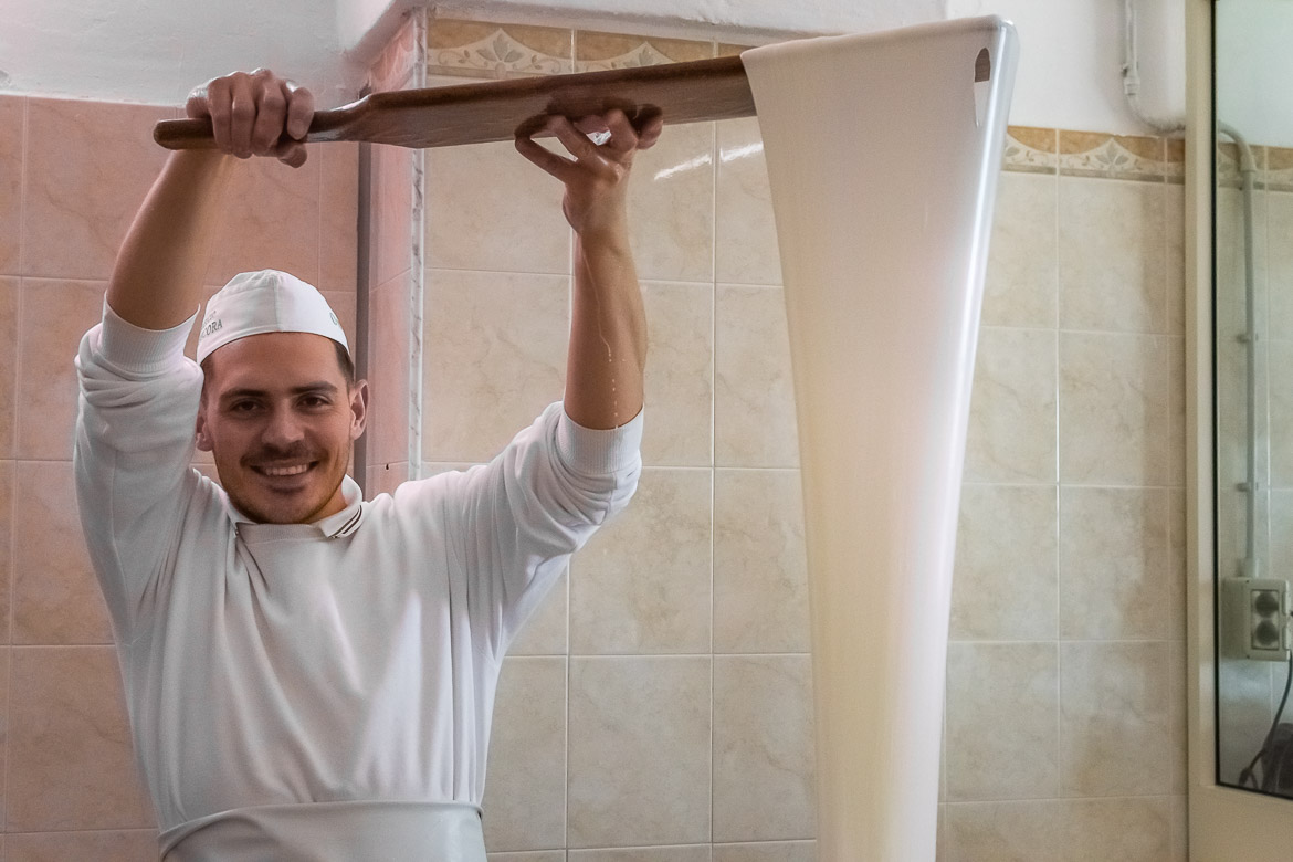 This photo shows a man in the process of making burrata cheese.