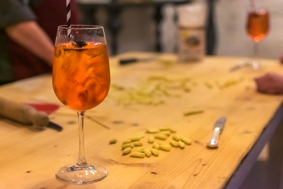 This is a close-up of the table on which we cooked during the cooking class. There is a glass of Aperol Spritz next to freshly made pasta.