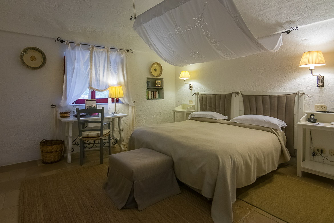 This image shows our room at Masseria Torre Coccaro. It is decorated in white and light grey. It is romantic, luxurious yet cosy with a traditional touch.