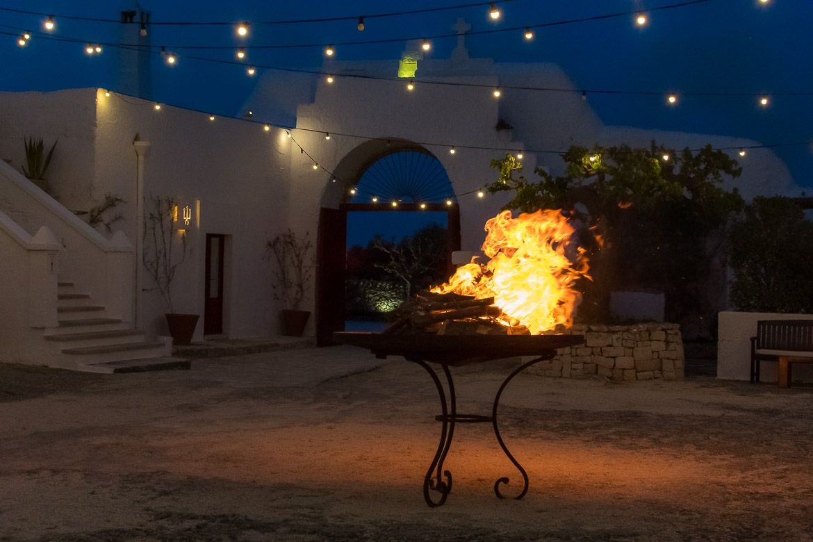 This photo shows the large central couryard at Masseria Torre Coccaro in the evening. There are lines of small lamps lit and also a big fire right in the middle of the courtyard.