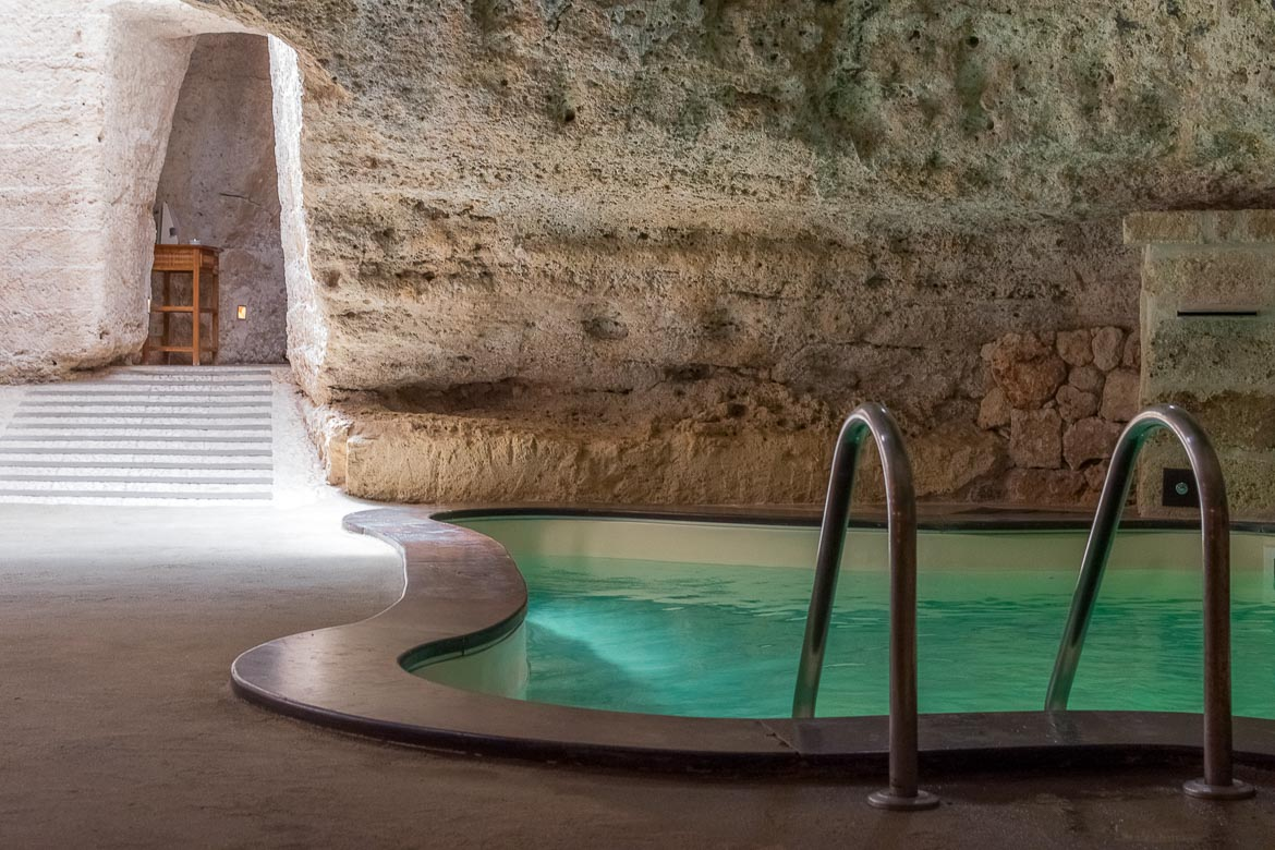 This image shows the indoor pool at Masseria Torre Coccaro. It is carved on the rock.