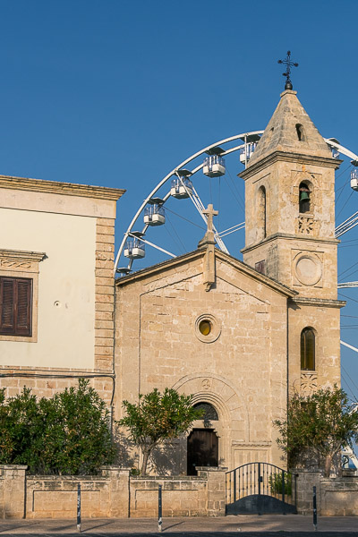This image was shot in Savelletri, a quaint tiny town. We can see an old church in front of a ferris wheel.