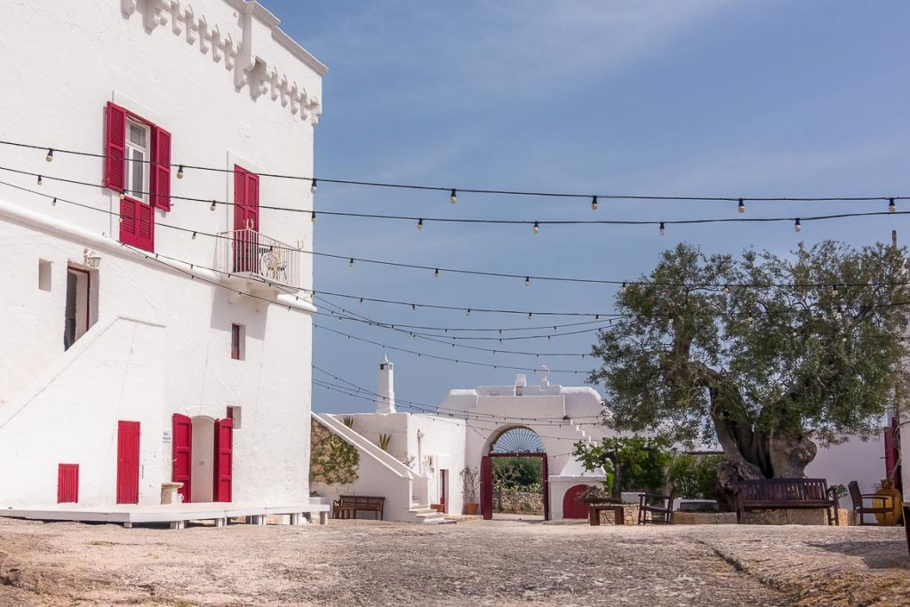 This photo shows the gorgeous central courtyard at Masseria Torre Coccaro. There is a whitewashed building on the left with bright red windows and doors. Masserie are typical to Puglia region. This is why we chose this photo to be the featured image of our article Best Places to stay in Puglia: An essential guide.
