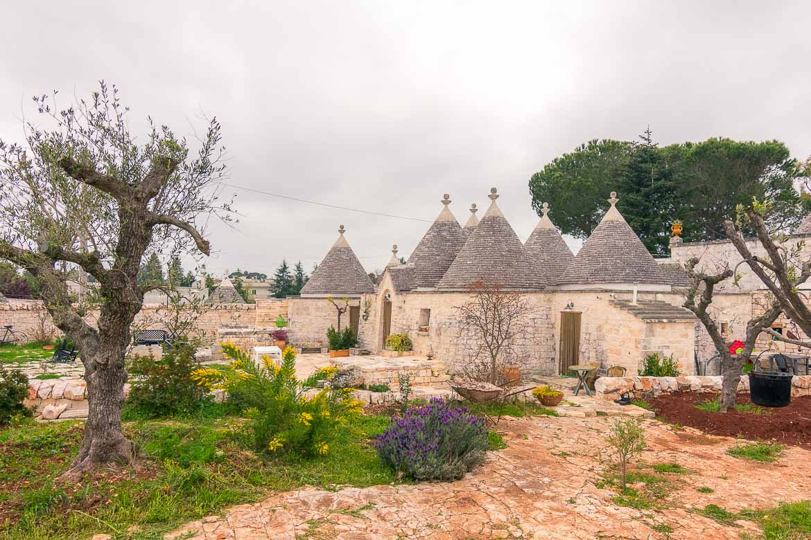 This photo shows a cluster of trulli buildings in the countryside.