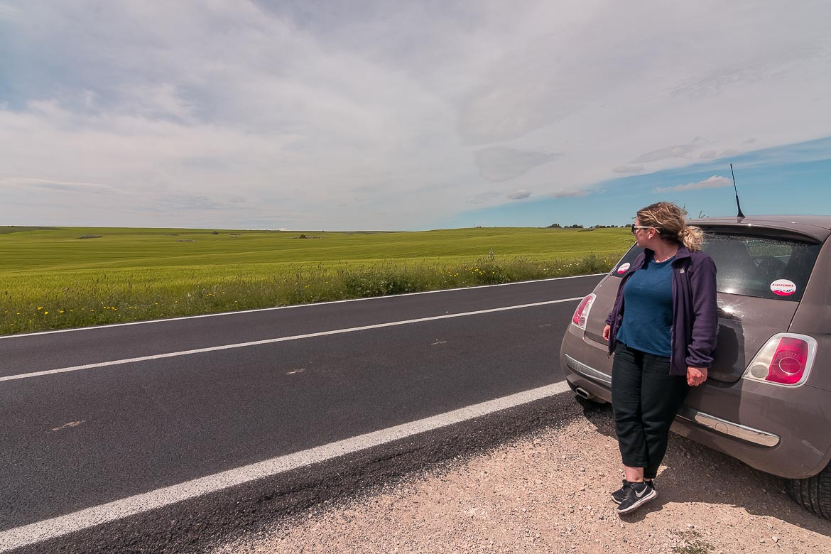 This image shows Maria leaning on the car, which is pulled over at the side of the road, marvelling at the amazing countryside around.