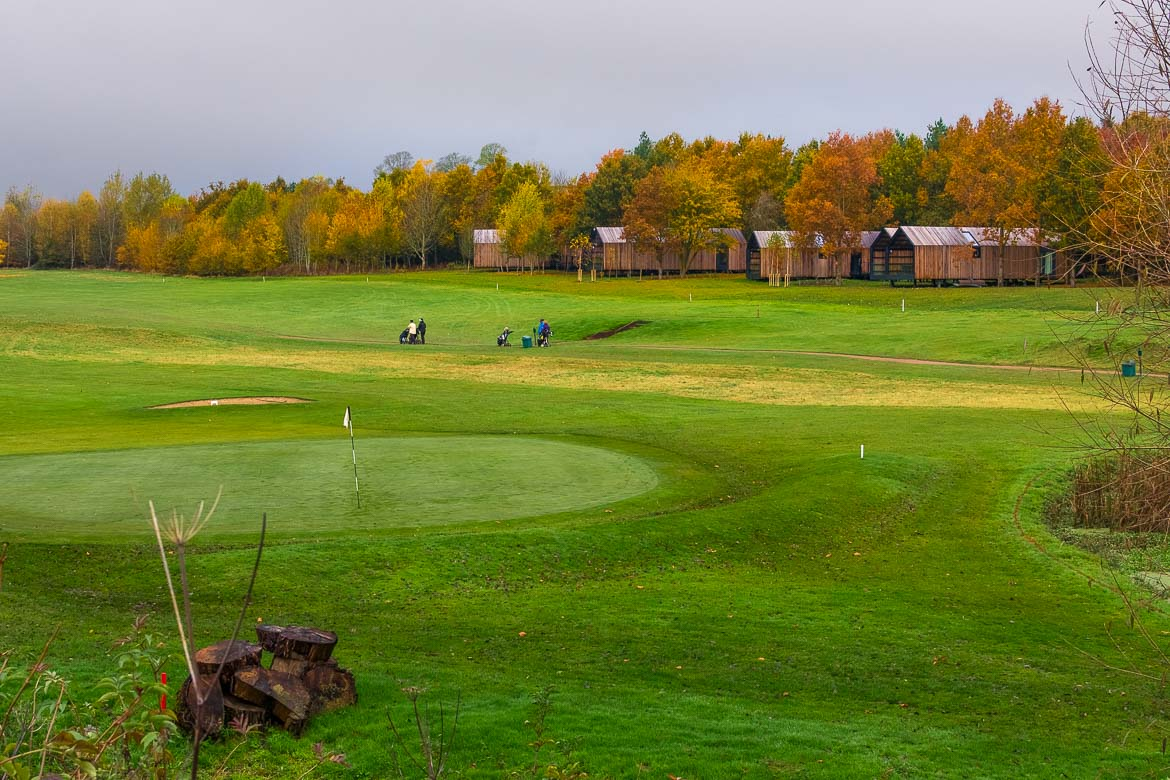 This image shows the golfing course at the Feldon Valley. In the background, the wooden lodges among beautiful green and brown trees.