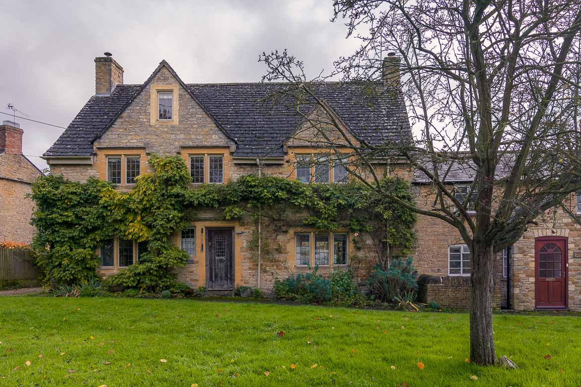This photo shows a traditional stone house with a splendid garden at Kingham.
