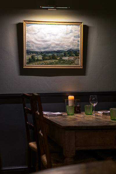 This is a close up of a table at the Kingham Plough restaurant. The furniture is vintage and there is a painting of the Cotswolds on the wall.