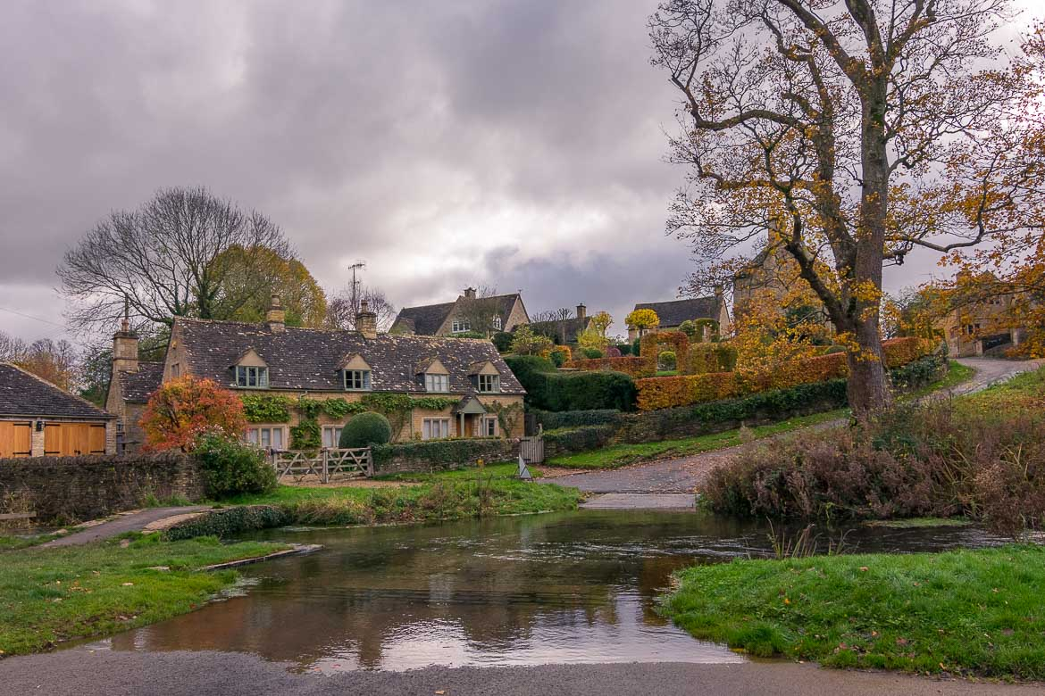 This is a photo of Upper Slaughter. There are beautiful honey-coloured cottages, a stream and autumn leaves everywhere.