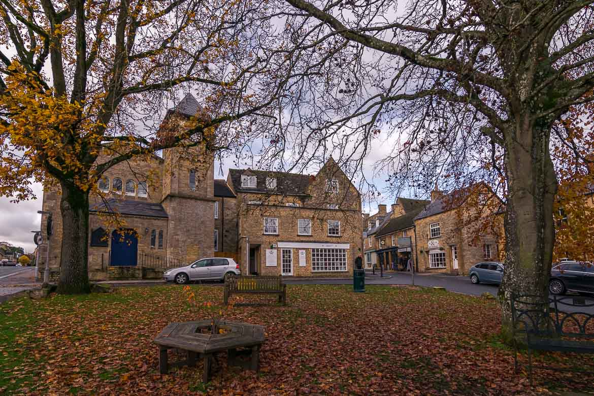 This is a photo of Stow-on-the-Wold. The buildings are honey-coloured and there are autumn leaves on the ground.