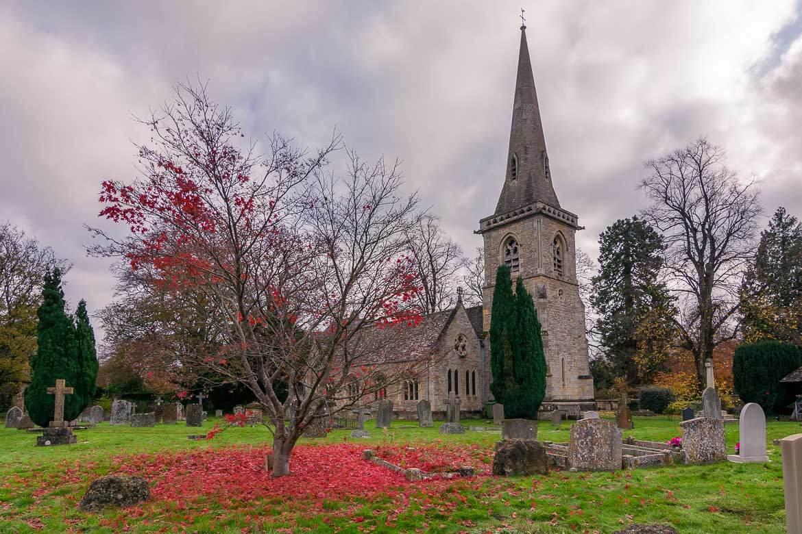 This image shows the Church of St. Mary the Virgin in Lower Slaughter. The church has a beautiful tall spire and there are many old tombstones on the green grass that covers the church yard. Central to the photo a beautiful tree that sheds red leaves on the ground around it on this cloudy autumn day.