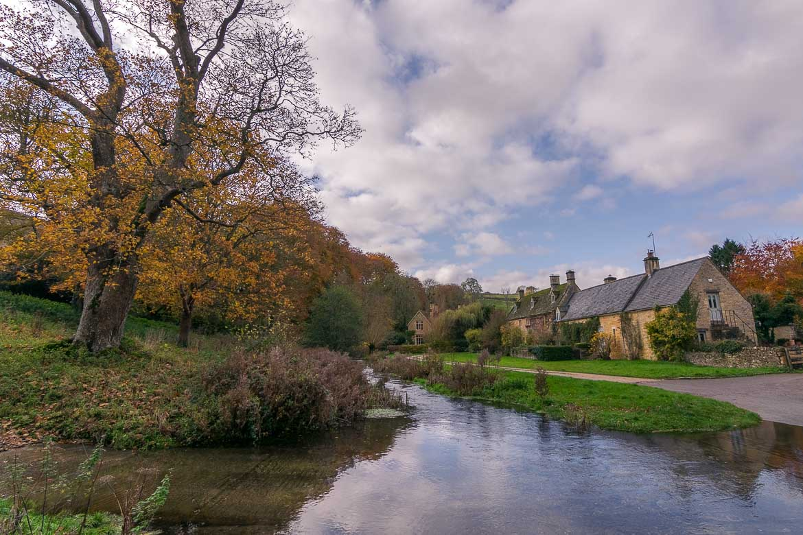 This is Upper Slaughter, one of the prettiest villages in the Cotswolds. It is autumn, the leaves of the trees are brown-orange. There are a couple of honey-coloured cottages to the right. In the middle of the photo, we can see the ford, a narrow stream at one of the village's crossroads. We consider this a very representative image of the Cotswolds. This is why we chose it as the featured image for our article Best villages in the Cotswolds: A complete guide.