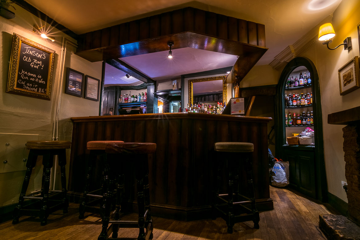 This is a shot of the interior of the White Hart pub in Castle Combe. There is an old fashioned bar with stools and the place feels very warm and cosy.