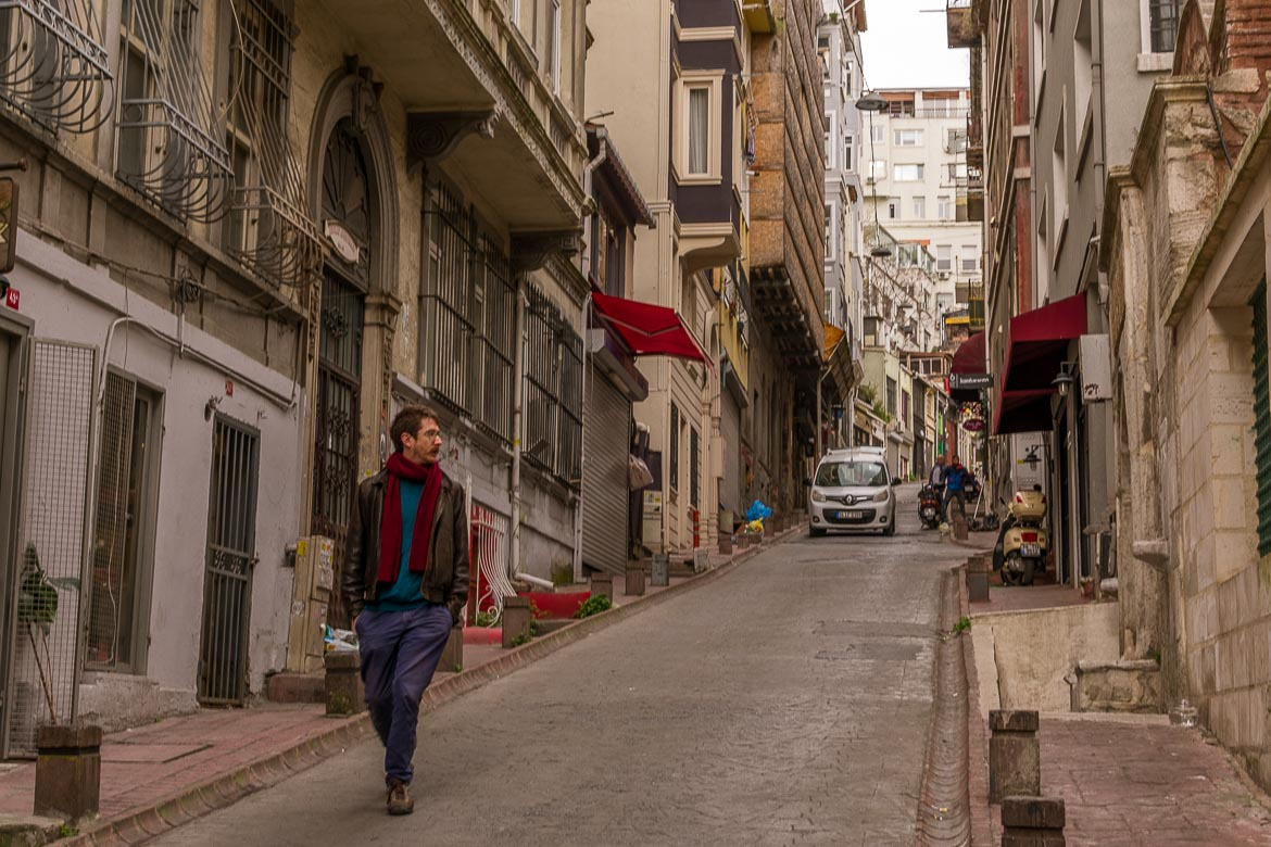 This image shows a man walking down a quaint uphill street in Beyoglu. The man is wearing a red scarf and this is a lovely contrast to this grey cloudy morning in Istanbul.