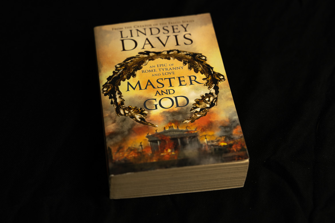 This image shows a paperback edition of Master and God by Lindsey Davis, one of the best historical fiction books set in Italy.
