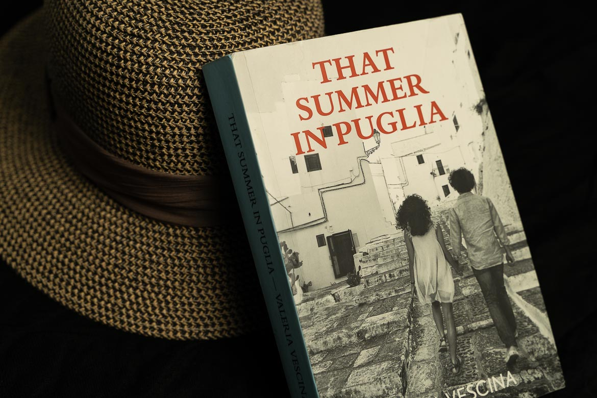 This image shows a paperback edition of That summer in Puglia by Valeria Vescina. The book is leaning against a straw summer hat. It's one of our favourite novels set in Italy.