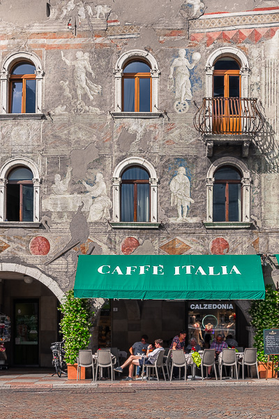 This image shows a beautiful facade in Trento. There's also a traditional Italian cafe where people are sitting on a sunny day.