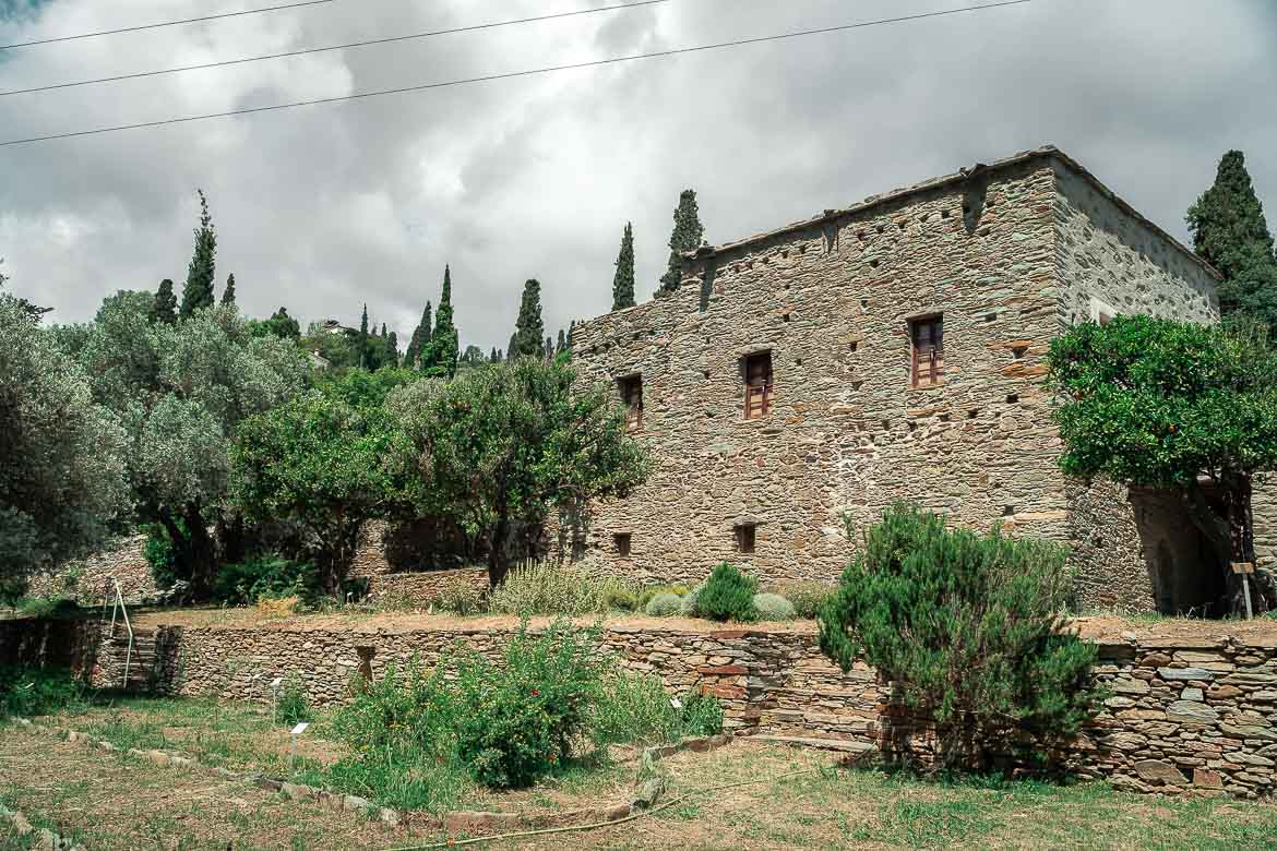 This image shows the restored stone tower amid olive and other trees at Agadaki Estate.