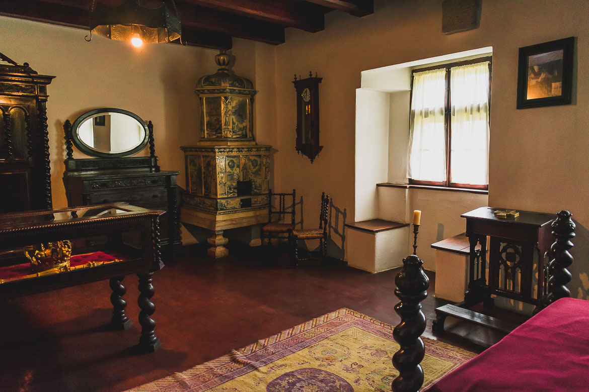 This photo shows King Ferdinand's bedroom inside Castelul Bran. The most beautiful piece in the room is the traditional Romanian tiled stove. Plan a trip from Brasov to Bran Castle!