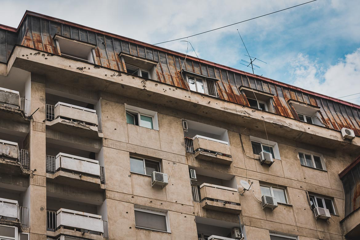 This photo shows the great number of bullet holes on buildings near Revolution Square. Bucharest walking tour of Communism, Romania.